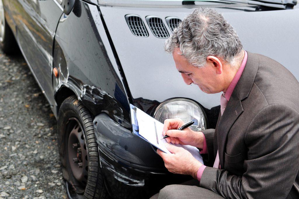 Schaden am rechten Kotflügel eines schwarzen Autos, im Vordergrund Mann mit Klemmbrett. Fahrerflucht Unfallaufnahme