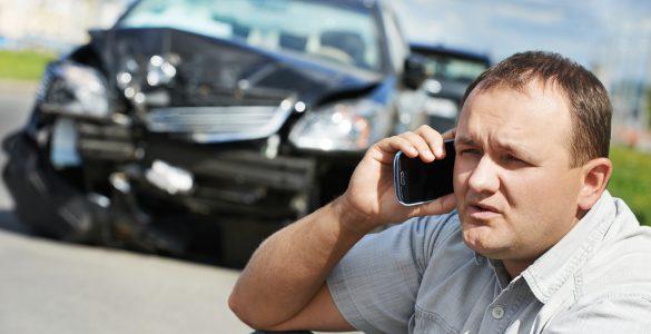 Mann im Vordergrund telefoniert genervt, im Hintergrund sieht man Unfallfahrzeuge.