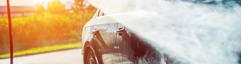 Auto wird mit einem Dampfstrahler behandelt, idyllisches Bild, Sonnenuntergang im Hintergrund